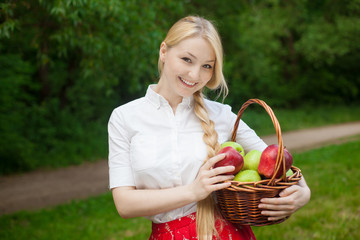 girl holding basket with red and green apples in the park