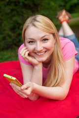 blonde girl outdoor in the park using her cell phone