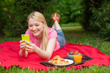 girl outdoor in the park on picnic using her cell phone