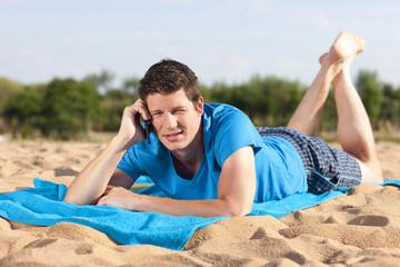 Junger Mann mit Smart Phone am Strand
