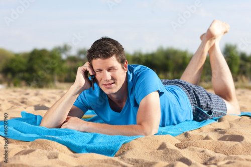 canvas print picture Junger Mann mit Smart Phone am Strand