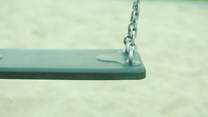 Childhood. Empty chain swing on playground.