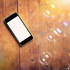 Closeup of smart phone and bubbles on wooden surface