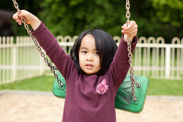 Cute little girl playing swing