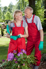Couple hug each other while working in the garden