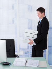 Businessman Carrying Stacked Binders At Desk