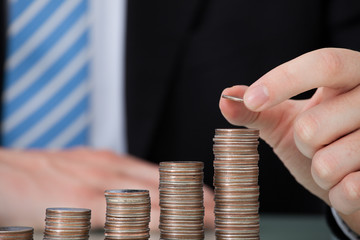 Businessman With Coins Stacked As Bar Graph