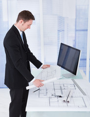 Businessman Looking At Blueprint At Computer Desk