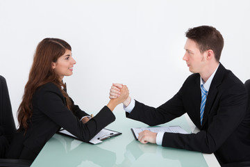 Business People Arm Wrestling On Desk In Office