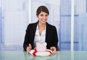 Confident Businesswoman Protecting Piggybank With Lifebuoy