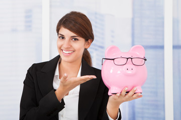 Businesswoman Showing Piggybank With Eyeglasses