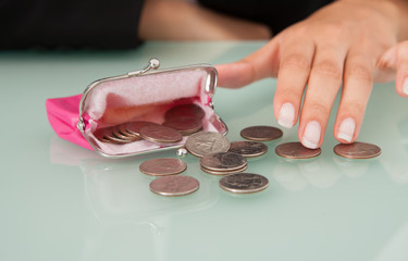Businesswoman With Coins Spilled From Pink Purse