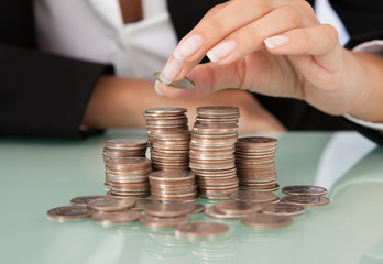 Businesswoman's Hand Stacking Coins At Desk