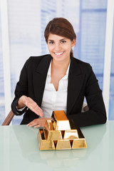 Confident Businesswoman Showing Stacked Gold Blocks On Desk