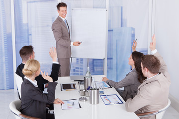Businessman Giving Presentation To Colleagues At Office
