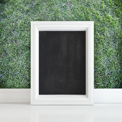 Black board in white frame on a white floor near grass wall