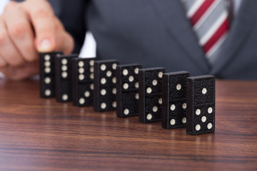 Businessman Playing Domino On Desk