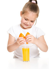 Cute girl is drinking orange juice