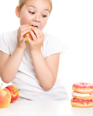 Cute girl choosing between apples and cake
