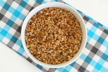 Cooked buckwheat in bowl on checkered cloth