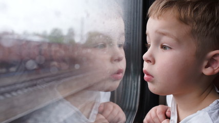 Curious boy looking out of the train window in rainy weather