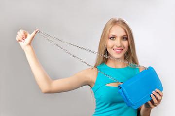 Красивая блондинка с синей сумочкой в рукх