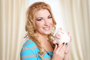 lächelndes hübsches Mädchen mit weißem Sparschwein