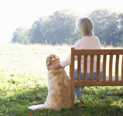 Senior woman sitting outdoors with dog