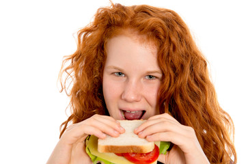 red haired girl eating sandwich