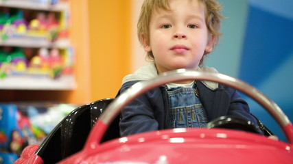 Little boy swinging in a toy car in the shop