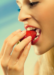Young woman eating strawberry on sea beach