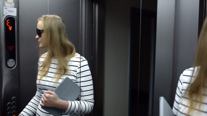 Young woman in the lift primping and make funny face