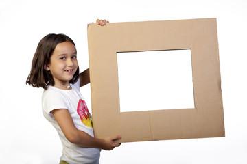 Niña sosteniendo marco de cartón