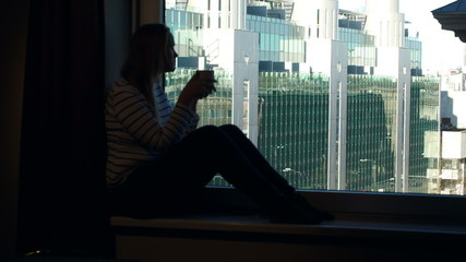 Woman drinking coffee on the windowsill with city view in the