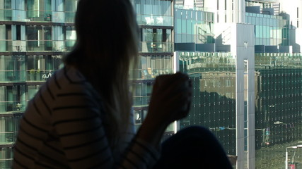 Woman at the window with mug looking at the city with modern