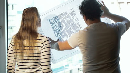 Two architects discussing a project looking at the city with map