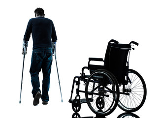 injured man  with crutches  walking away from  wheelchair silhou