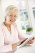Senior woman using tablet at home
