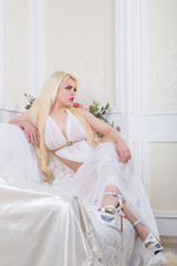 Luxurious blonde woman in a white dress