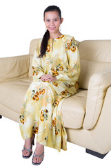 Female Asian lady in yellow dress sitting on a sofa