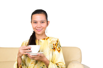 Asian Malay female holding a cup of hot drink sitting on a sofa