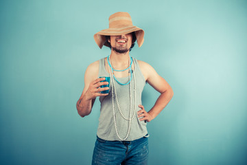 Happy young man wearing beach hat is drinking