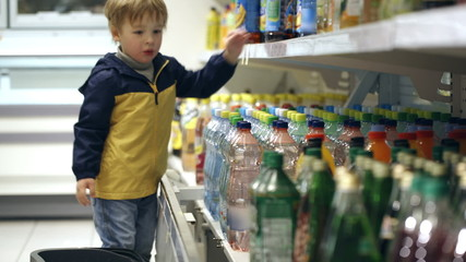 Little boy in the shop putting mineral water into the basket