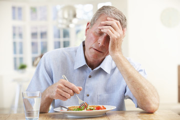 Sick older man trying to eat
