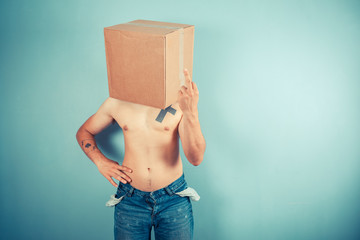 Man with cardboard box on head displaying obscene gesture