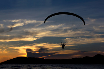 Silhouette paramotor / paraglider flying  on the sky with seavie