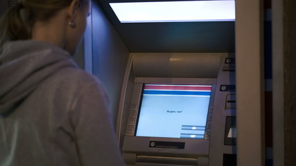 Woman using ATM outdoor in the evening