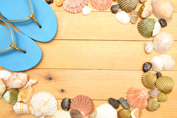 Beach slippers and shells on wood