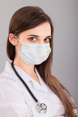 Doctor / nurse smiling behind surgeon mask. Closeup portrait of