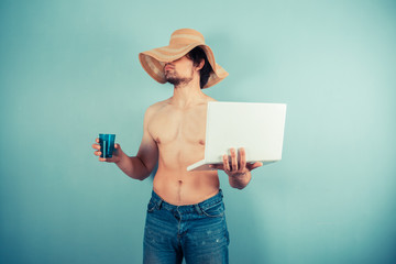 Young shirtless man with cup and laptop